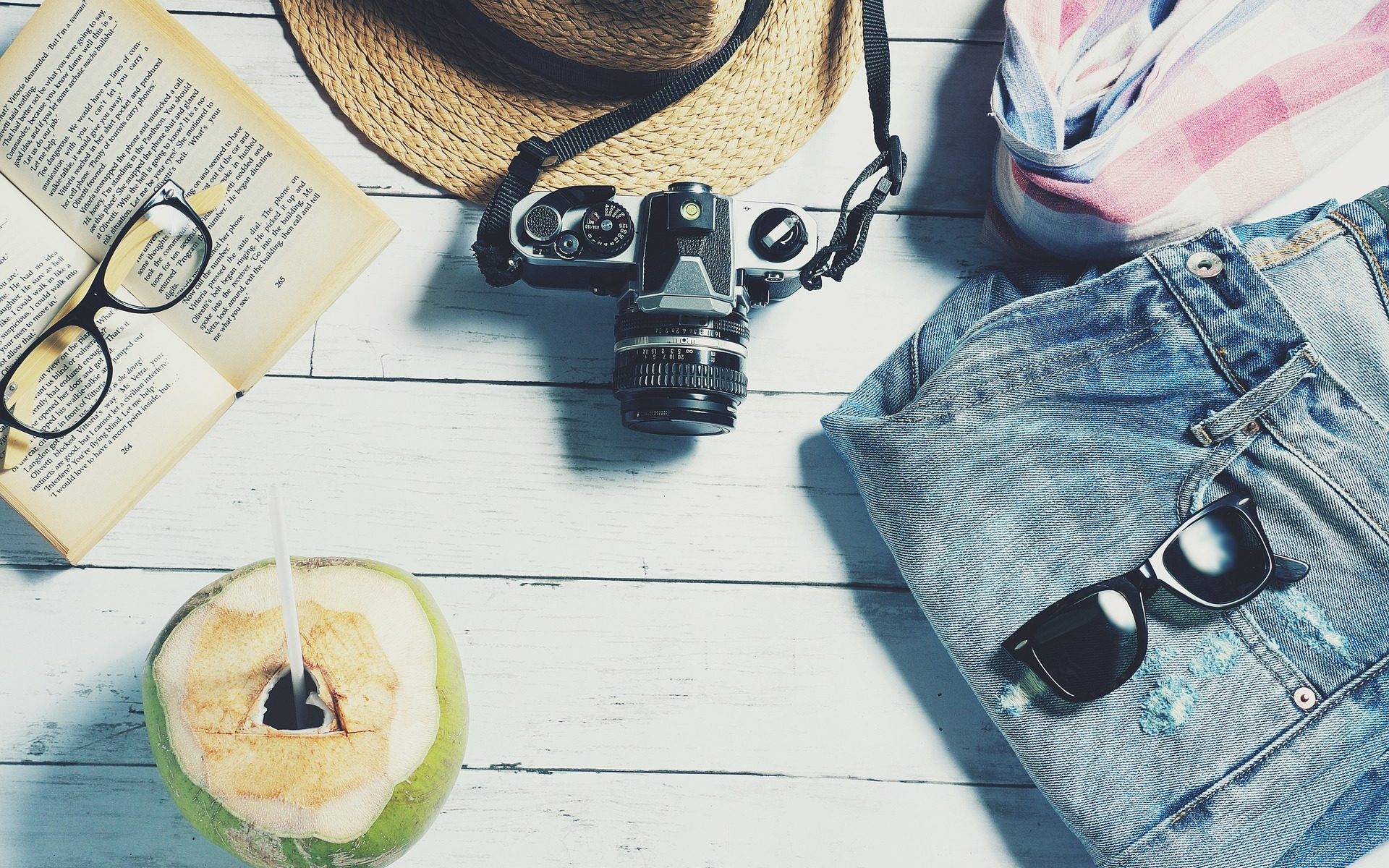 melting pot d'objets de vacances : lunettes, appareil photo, chapeau...