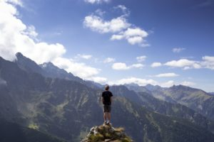 Un homme en haut d'une montagne contemple l'ohrizon